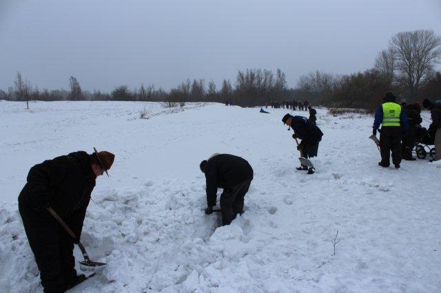 Industribaneklubbens folk og en spejder skovler sne fra omløbssporet