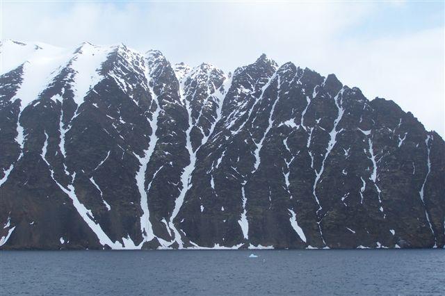 Et fuglefjeld på afstand som man også ser det fra Hurtigrutens skibe. Ved man det ikke, opdager man det ikke.