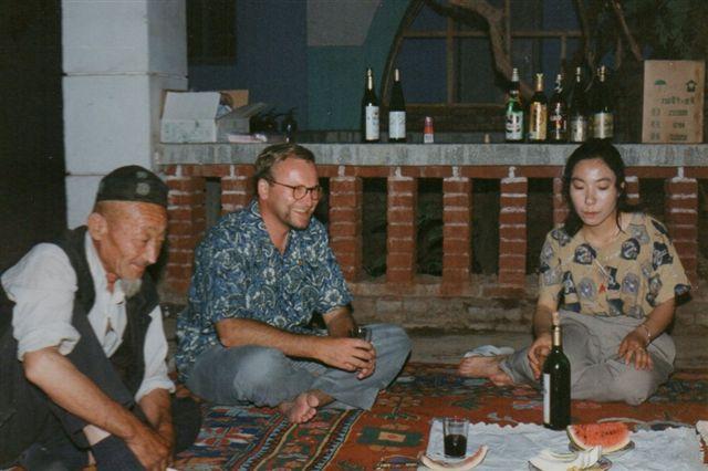 I vingården, der omgav det forlængst nedrevne hotel i Turfan, hygger vi os med lokal vin og lokal mad en aften i 1995. I midten sidder en dansker og til venstre en gammel hankineser, der passede vingården og sov derude. Han var for længst gået til ro, men vi kom til at vække ham, og han sagde ikke nej til et glas.
