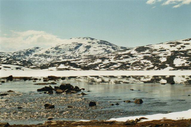Bjerget i baggrunden ligger i Norge. Søen her gik vi dog uden om. Det var vindstille, så vi gik i undertrøjer og spiste i bar overkrop. Mest fordi tøjet var vådt af sved. Det lå til tørre i solen.