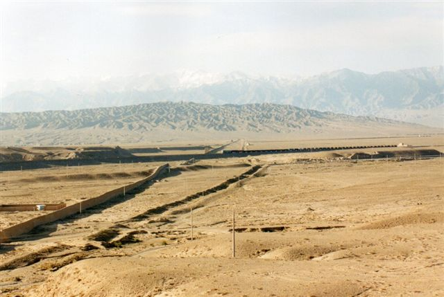 Spærringen over Gansukorridoren var til dels ødelagt, men man aner en svag murrest over til bjergkæden i det fjerne. Grøften kan være en historisk udgravning? En voldgrav ville vi kalde det, men det kneb lidt med vand her i ørkenen. Midt gennem området fører jernbane til Xinjiang, Uzbekistan og Kasakhstan. Der kører et godstog på banen lige i fotoøjeblikket.