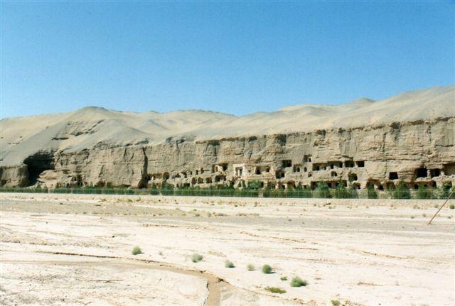 Klippeklostrene i Dunhuang. Der var ikke mere vand i floden, end vi ser her, men der kunne undertiden være mere. Kalkvæggen i baggrunden er udhulet. Her boede buddhistmunke indtil islamister dræbte dem for omkring tusinde år siden. Andre huler var begravelseshuler. I mange er vægmalerier bevaret gennem 1500 år næsten uden farvetab. Derfor er området hegnet ind. Vil man kigge, må man betale entre. Jeg besøgte flere af hulerne, med en professor, der dels havde nøgle og dels var ligeglad med besøgsforbuddet i flere af de meste spændende huler. Jeg respekterede dog forbuddet mod at fotografere, så du må på nettet for at se buddhastatuerne og vægmalerierne. Jeg fik også en grundlæggende viden om buddhismen samt om historien bag mange af malerierne - lige til, der ikke var mere ram. Jeg i hvert fald kunne ikke rumme mere. Pas på, for stort set alle huletemplerne langs Silkevejen kaldes lokalt for De tusind Buddhaers Hule - undtagen én, der kaldes de titusinde Buddhaers Hule.