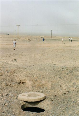Karezerne blev fødet med vand fra de fjerntliggende Tianshanbjerge. Her ses en rensebrønd. Måske er der nogen dernede. I det fjerne ses endnu et muldvarpeskud, men de skulle ligge en hel række. En støvstorm forhindrer os i at se hele rækken af muldskud. 1999.