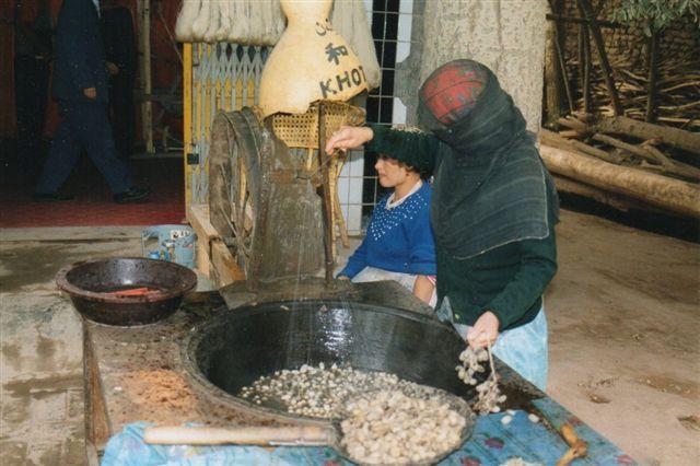 Silketrådsopvikling i Kashgar 1999. Pupperne ligger skålen og puttes derefter i det varme vand, hvor de dør, og silketråden kan vikles op på hjulet i baggrunde. Den nærmeste, ret tilslørede kvinde holder styr på trådene, så de ikke filtres, og den anden drejer hjulet. Der demonstreredes også silkevævning på markedet.