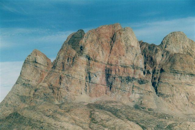 Uummannaqfjeldet tættere på. Det mere en en kilometer høje fjeld består af 3 milliarder gamle gnejer foldet sammen med 2 milliarder gamle sedimenter. Sider er folderne kommet til at ligge ned. Der er en fold i det sorte bånd øverst, og en nok så markant fold i det næsttykkeste bånd under neden. Prøv at følge båndet! Og så tænk dig, at det var dig, der skulle vride dette bånd......