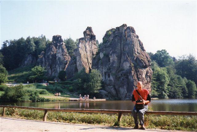 """Externsteine. I bjergkæden fandtes også disse lodretstillede sandstenslag, der havde været udnyttet både af en herremand og af munke. Nu arbejdede stenene i turismens tjeneste. Der var hugget huler og gange og lavet trapper og træbroer mellem """"tårnene."""" Med lidt meget god vilje anes personer på toppen af en af klipperne."""