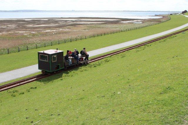"""Foto i Lüttmoorsiel af """"mit"""" særtog bestående af en åben og en lukket motortrolje samt en bænkevogn. Deltagerne fotograferer, så toget er her næsten tomt."""