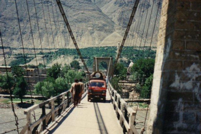 Hængebro bygget af englænderne i Gilgit over Gilgitfloden. Moskeen ses. I baggrunden de golde bjerge. Bemærk den grønne streg, der markerer en vandingskanal, der opsamler smeltevand fra bjergene og leder det til kunstvanding i dalen.