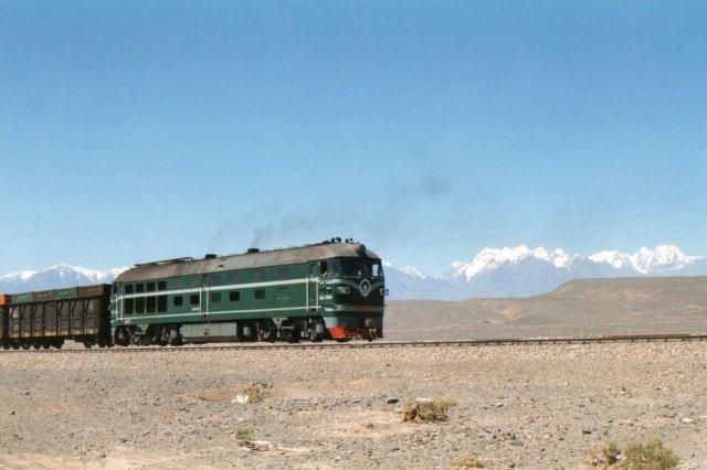 DF med ukendt underlitra 7283 foran et godstog med 50 fireakslede vogne, hvoraf flere maskinkølevogne med indkoblede mandskabsvogne. Vi er i Taklamakanørkenen og ser Tienshan, Himlens Bjerge i baggrunden. Året er 1995.