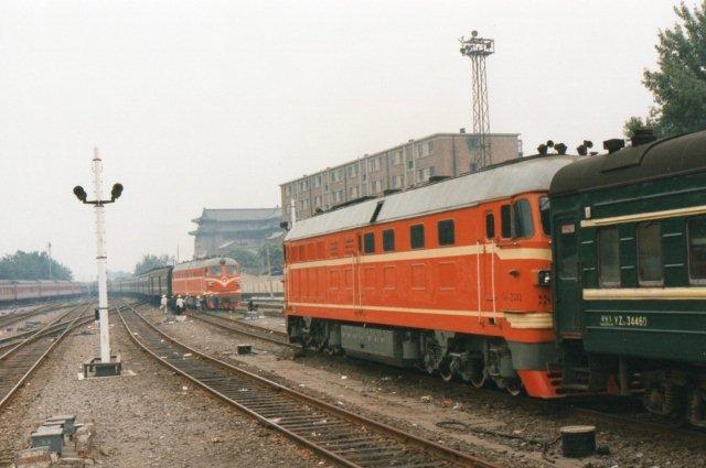 Vi er stadig i Beijing 1995. Til venstre afgår BJ 1660 og 1680 med 15 vogne. Til højre ankommer DF 2477 ligeledes med 15 vogne. Klar til afgang holder DF 4 2332.