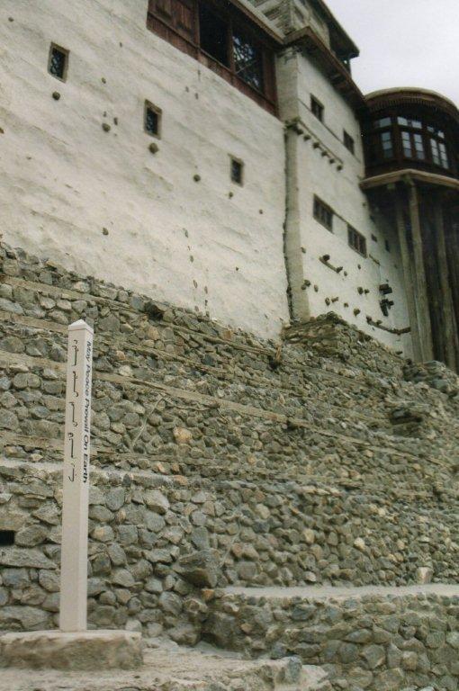 Dele af den gamle borg med stelen foran.