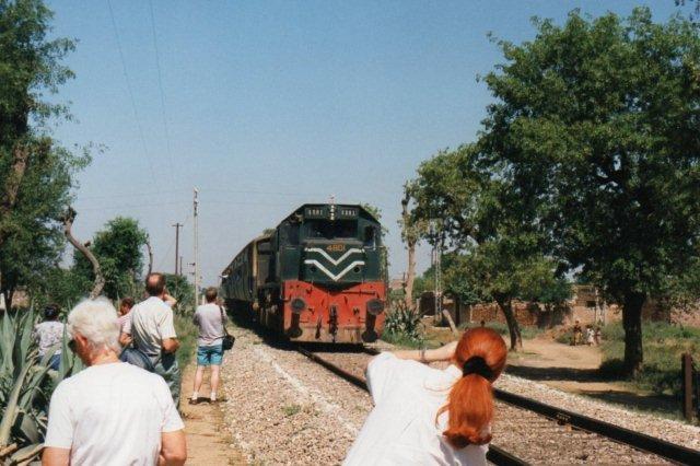 Samme data, som 4802 og 03, som jeg også så. Her holder vi for bomme, og jeg fik lov til at stå ud bussen, for at fotografere toget lige før Haripur mellem Taxila og Havelian. Og så myldrer de civile ud og står i vejen, også selv om de ikke er jernbaneinteresserede. De gjorde det først, da det var for sent at flytte sig endsige at råbe op! Damen til venstre havde vist også opdaget, at der voksede vild hash mellem agaverne.