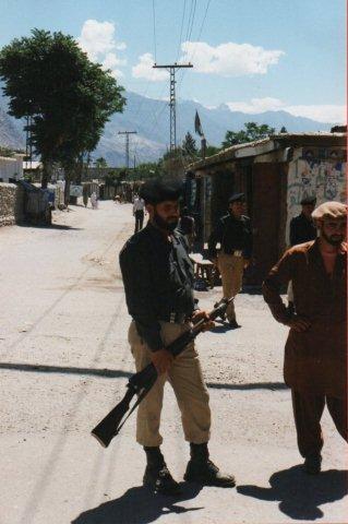 En politisoldat. Ikke ham, der demonstrerede sit gevær. I baggrunden en sort shiafane over et hus.