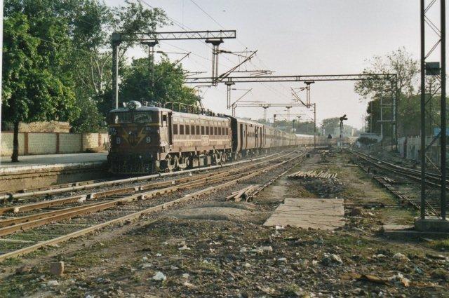 Et langt tog fremført af et elektrisk lokomotiv susede gennem Agra Ford Station og gjorde livet farlig for indfødte, fotoaber, aber og hellige køer.