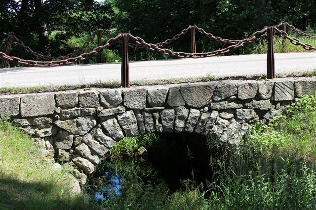Stenen stod på en ø i en lille bæk, der løb ud i grænseåen. Broen er dog af nyere dato. For 35 år siden var jeg her også, men da var der grusvej og ingen turister. Det havde nu ændret sig.