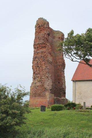 """På Pellworm er der to kirker tilbage, som stormfloderne endnu ikke har taget. Tårnet her, der tidligere var dobbelt så højt, styrtede sammen """"af sig selv"""" og ikke på grund af en stormflod. En tårnfalk havde rede her mellem duerne."""
