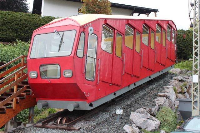 Som blikfang ved Achenseebahn stod dette tog uden nogen data. Fra Achenseebahn er den i hvert fald ikke, idet stigningen her langt overstiger 16 %. Vognen er da også en spilbanevogn, nr. 1 i øvrigt fra Hungerburgbahn i Innsbruck. I følge bykort over Innsbruck er denne bane moderniseret temmelig kraftigt, siden jeg kørte med den første gang i 1953. Ved siden af dette blikfang/denkmal stod også nogle rester af tømmervogne - det hele godt gemt bag hensatte biler. Jenbach 01.09.2013.