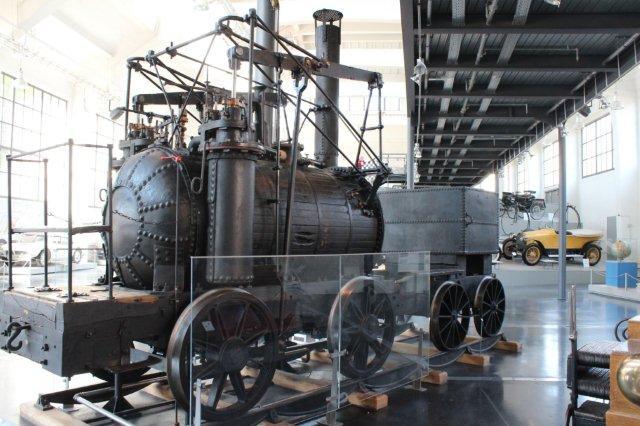Trafikmuseet i München havde også en kopi af verdens første brugbare lokomotiv, Puffing Billy fra 1814. Originalen står i London på South Kensington-Museet. Kopien her er bygget med en kedelbeklædning, hvor selv mørnede beklædningsbrædder er gengivet! William Hedleys lokomotiv kørte ved Wylam-kulminen 1814 - 1862. Det var på 25 hk, havde en vægt på 9,19 t uden tender og kunne køre 10 km/t. Kopien er bygget i Tyskland til museet i München i 1906. Foto fra 30.08.2013.