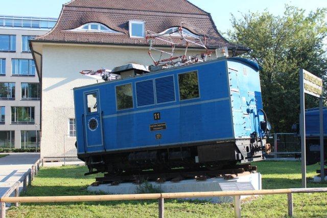 Tandhjulslokomotiv fra Bayrische Zugspitzbahn AG nr. 11. AEG 4260/1930. Der var 8 bjerglokomotiver, 11 - 18. Hvert lokomotiv havde tre tandhjul hver med en motor på 170 kW, altså 510 kW. Vægt på 27,5 t. De kørte 13 km/t opad, men kun 9 km/t nedad og kun med to vogne. Når Riggenbachsystemet ofte ses med to eller tre forskudte tandstænger, er det, fordi hver motor arbejder med eget tandhjul på sin egen tandstang. München 30.08.2013. I dag kører banen med motorvognssæt.