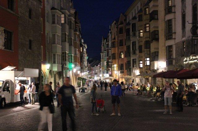 Et stemningsbillede fra byen. Her var ikke uden charme, nogle har trøjer på. Alperne havde taget noget af Sydtirols hede. Vi sad dog ude i korte ærmer og spiste på cafeen til højre. Det er helt mørk, så folk, der bevæger sig, bliver uskarpe.