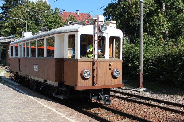 Halvtimedriften krævede to tog. Det andet var en motorvogn med en alder af 104 år. Den var naturligvis vedligeholdt, og vitale dele som bremser var opdaterede. Også den ses her ved ankomsten til Klobenstein 31.08.2013. Nummeret er 105, og vognen er bygget af Nesseldorfer Waggonfabrik 1910 med 24 tons vægt, 70 hk og 25 km/t som højeste hastighed. Den er købt brugt fra en anden bane.