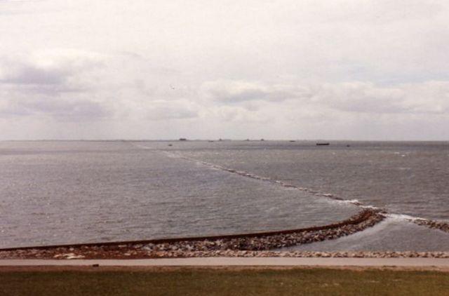 Billedet her er taget 1986, hvor banen til Nordstrandischmoor forlader Lüttmoorsiel. Det er højvande noget over det daglige højvande. Muligvis er det springflod eller en nipflod forårsaget af fuld- eller nymåne, men storm er der ikke tale om. Måske en fjern storm har presset vand ned mod Vadehavets kyst. En dag, hvor vandet stod endnu højere, skulle en lille gruppe skulle have været på en tur med banen, men turen blev aflyst.. Jeg nåede telefonisk at blive advaret, men deltagere fra Hamburg var allerede taget hjemmefra. Siden er banen blevet hævet 75 cm, så den i dag er tør også ved nip- og springflod.