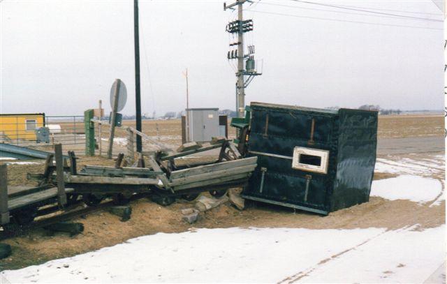 Ved et andet besøg havde det dog stormet om natten. Da det tyske kystbeskyttelsesvæsen muligvis ikke var helt færdig med diget omkring Beltringharderkoog eller endnu ikke stolede helt på det, havde de kørt en del af materiellet op på digekronen for at beskytte det mod et eventuelt højvande bag diget. Vinden om natten havde imidlertid blæst vognene ned fra diget. Selv på jorden væltede stormen vognene, men her faldt de ikke så langt. I dag er der bygget en materielgård med en stor hal. Diget for Beltringharderkoog havde forkortet banen med tre kilometer, så den gamle materielgård med remiser var allerede lukket og sporet dertil taget op. Den nye materielgård var endnu ikke påbegyndt. Fotoet er fra Cecilienkoog 1986.