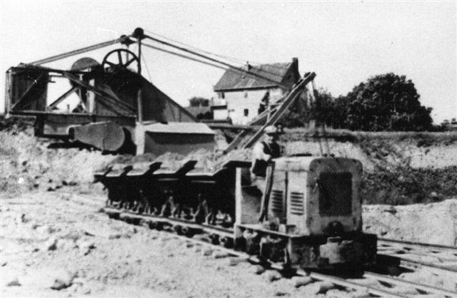 Molbograven lå i 1965, hvor billedet er taget, lidt fra værket i et villakvarter. Lokomotivet er et Henschel. Billedet er lånt på Viby Bibliotek.