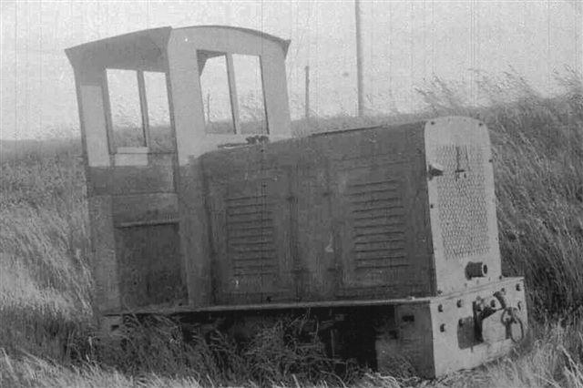 """Nærbillede af Henschellokomotivet. Billedet er taget af Hartvig Albrekt først i 1960'erne. Jeg var der i 1966 og så lokomotivet. Jeg kendte ikke den type, men nogen havde sat et """"Henschel-diesel-skilt"""" på køleren, og det troede jeg ikke på. Senere, da jeg for alvor begyndte at arbejde sammen med udenlandske forskere, blev det klart, at lokomotivet var fra Henschel. Skiltet var dog fra en lastbil. Vi kender desværre ikke byggeår på lokomotivet, der var uden byggeplade bortset fra, at det er en Henschel DG 13 altså med 13 hk og af den lille type. Formentlig var byggenummeret 17261."""
