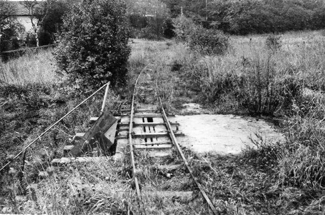 Banen blev afkortet i flere omgange, så der til sidst kun kørtes med tog i graven. Lastbiler havde overtaget resten af banens funktion. Her ses læsseanlægget til lastbiler ude ved graven. Grunden til afkortningen var, at dele af banen allerede var blevet udstykket til byggegrunde. Foto: SAG 1964. Han vendte tilbage 1968, men banen var da helt lukket. Jeg var der i 1966, men da var alt uforandret, men det menes, at driften stoppede i 1966.