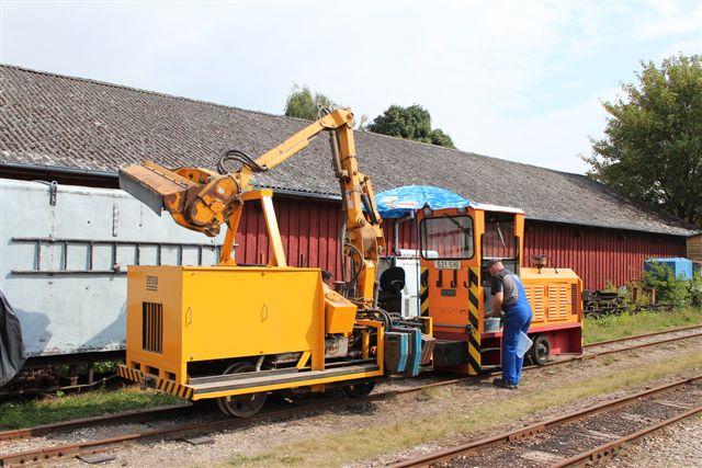 Vort nye lokomotiv stadig med nummerering fra kobbersmelteværket i Lünen er i Hedeland indsat af banetjenesten blandt andet til klipning af græs og trævækster langs banen. De kræver to mands betjening. En kører lokomotivet og en klippemaskinen. Klippeagragatet betjenes fra en svingbar kontorstol monteret bag på lokomotivet. Til værn mod brændende sol har han en parasol. Begge dele anes på fotoet.