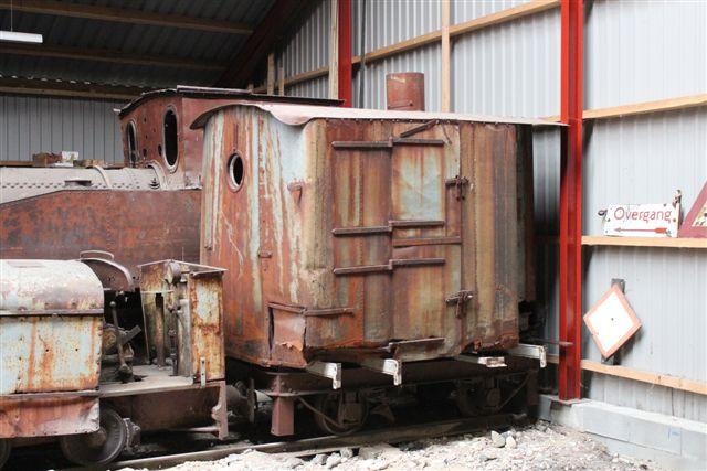 En vognkasse fra et mere end hundrede år gammelt motorlokomotiv. Godt nok uden motor undervogn, men ikke umulig at få ud at køre igen. Det er hovedsagelig tid og mandskab, der mangler.