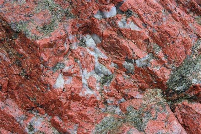 Nedenunder ses både den røde feldspat og linser af ren kvarts samt rester af endnu uomdannet gnejs.