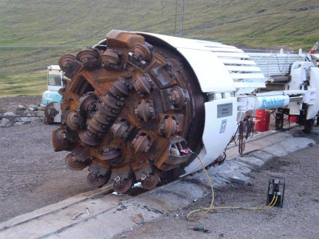 Borehovedet i nærbillede. De små hjul trykkes med stor kraft mod fjeldet og knuser dette, og stumperne falder gennem hullerne i borehovet og transporteres bort via transportbånd og tipvognstog. Foto fra starten 2010 af Edmund Hansen.