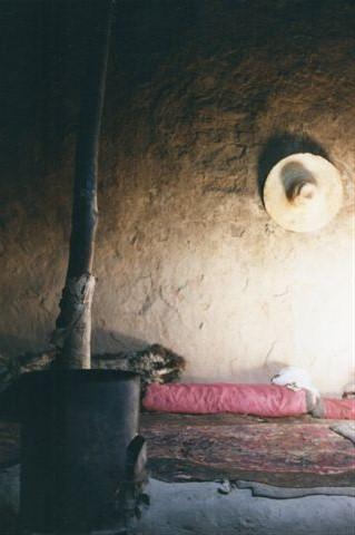 Husets stue. En ovn og en forhøjning som sofa, men der er ægte tæpper?
