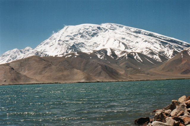 Dette bjerg, Muztagh Ata, Isbjergenes fader, 7546 meter, Kinas tredje højeste bjerg beliggende i Pamir rummer adskillige gletschere, men nu er vi nede i 3300 meter, så der er højt op til gletscherne. Søen er Kara Kul, Den sorte Sø. På et andet foto af bjerget set fra en anden vinkel, ses 7 gletschere.