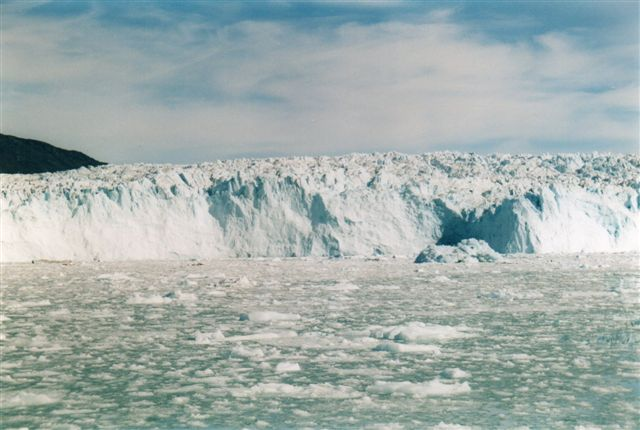 Eqibræen i Grønland 2014. Vi er i Atasund eller Ikerasak nord for Ilulissat. Gletscheren er 50 meter høj fra vandlinje til top. Den kælver ikke før den slipper bunden 350 - 400 meter under havoverfladen. Skipperen her holdt 2 sømils sikkerhedsafstand. Hver gang den kælvede, vippede vi voldsomt. Reklamefotoene fra turen var taget meget tætterepå, men sådan er det jo med reklamer.