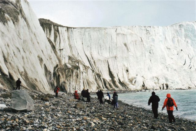 Her ville vi ikke med. Folkene er på veje langs stranden hen under 14. Julifjorden i fjorden af samme navn. vi er på Svalbard 2008. Det en sådan tur året før, der kostede en bekendt livet. Pludselig brød vand inde i gletscheren igennem og skyllede selskabet ud i fjordens isvand. Lederen af dette selskab her var endog glaciolog! I stedet fik vi en fugletur langs kysten. Skipperen var selv ornitolog, men han sejlede med kamra for øjet, og selv om vi råbte op, ramte han et skær. Vi overlevede dog, idet vi ikke faldt i vandet ved kollisionen.