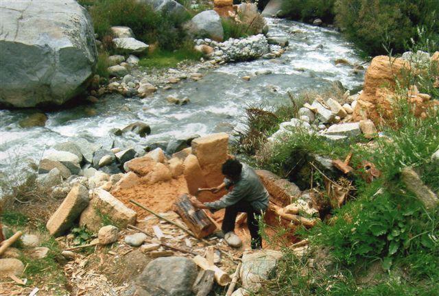 En arbejder lægger et harpiks- og røgelsesholdigt fyrretræstykke på plads i møllen så det smuldres på sandstenen i bunden. Bækken ser velvoksen u, men det var ikke direkte den, der leverede vandkraften.