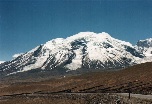 Muztagh Ata, Alle isbjerges Fader, 7546 meter, Kinas tredjehøjeste bjerg med Kara Kul søen i forgrunden. En prinsesse gik herop for at plukke blomster trods gudernes forbud. Guderne holdt hende derpå fangen, og hun græd, og hendes tårer frøs til is. Til højre anes ikke mindre end fire gletschere, der er ved at slide bjerget ned.