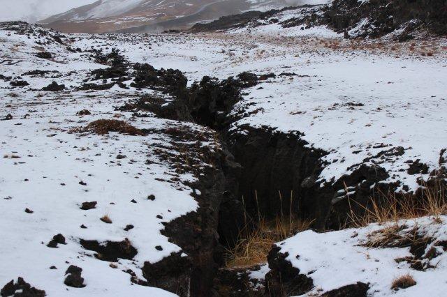 """Jeg går imens i naturen ved Mývatn. Jeg vil hen til dampudstrømningen i baggrunden, men en dyb spalte i jorden hindrede mig i at kommer derover. Guiden havde tidligere oplyst, at vi befinder os i Den midtatlantiske Rift. Det gjorde vi for så vidt også. Vi havde allerede fra bussen set flere af disse smårifter. De lå imidlertid på både kryds og tværs, så der var nok her snarere tale om domestrukturer. Under Island lå jordens glødende indre tæt på jordoverfladen. Ved Mývatn var et mindre område særlig tæt på lavaen. Denne løftede jordoverfladen som en kuppel, og derfor revnede jorden på kryds og tværs. Det var sådanne revner, jeg så. På Tenerife så vi dem som dykes og sills. Dykes er lodrette sprækker placeret frontalt eller vertikalt og senere opfyldt af opstigende lava. Herefter eroderes de omgivne ofte blødere områder, og den hårde lava står til bage som """"mure."""" Island er ung i forhold til Tenerife, så spalterne her er endnu ikke udfyldte og omgivelserne endnu ikke borteroderede. Det var nu, hvis jeg har ret, ikke den eneste gang jeg fik en skrøne, og det var ikke den eneste gang en guide havde divergerende opfattelser af geologien. Den midtatlantiske rift ses også nær Mývatn, men vi så den bare ikke."""