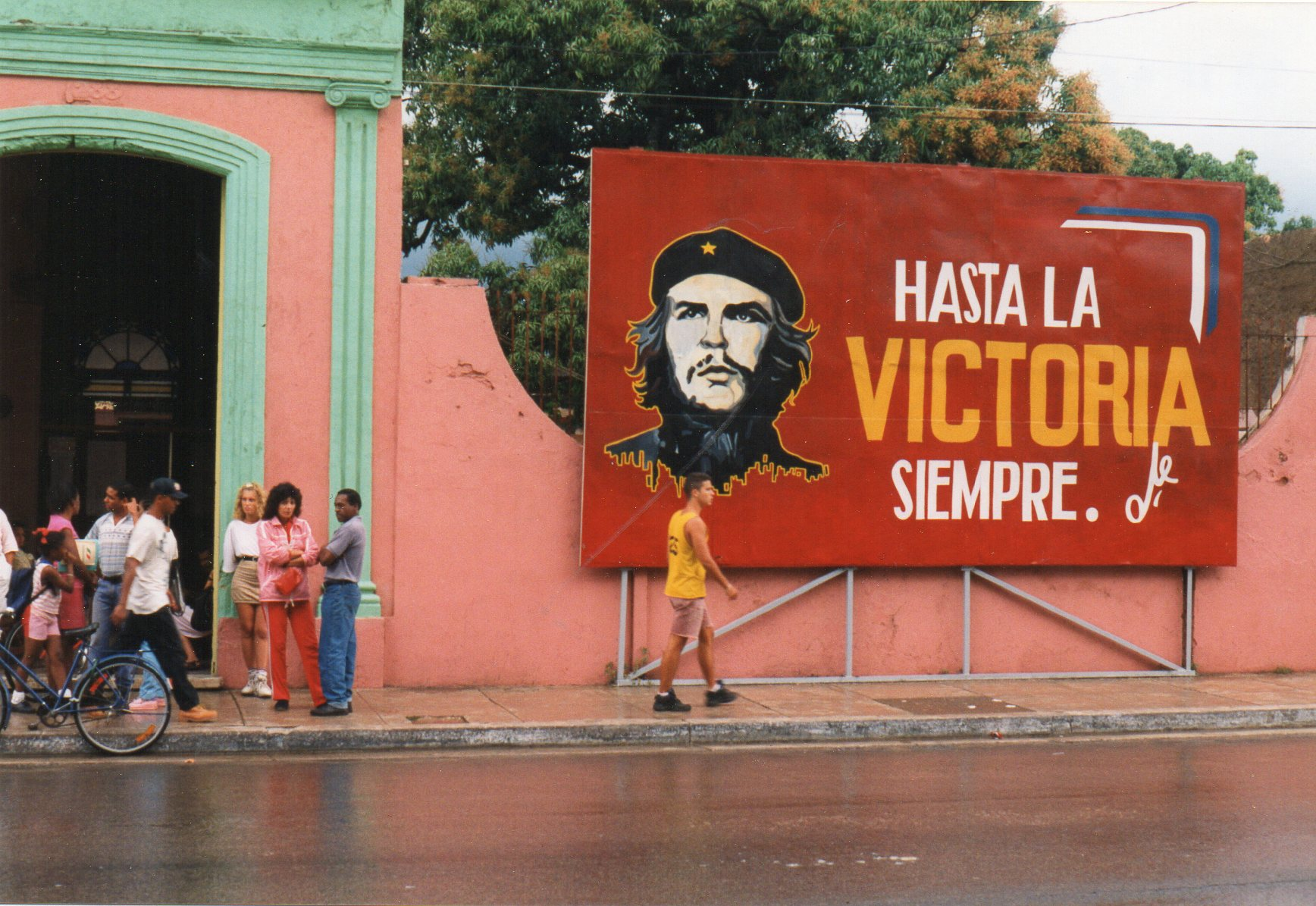"""Overalt på Cuba mødtes man af politisk probanada. Det var aldrig Castros kontrafej,men som oftest Che, der bevogtede en, som nu her ved en biograf i Cardénas. Normalt stod, der som her noget i retning af: """"Indtil sejren. Altid."""" Et enkelt sted sås et skilt med teksten fremdeles om Che: """"Dit eksempel vinder. Dine ideer taber!"""" Så fik han den."""
