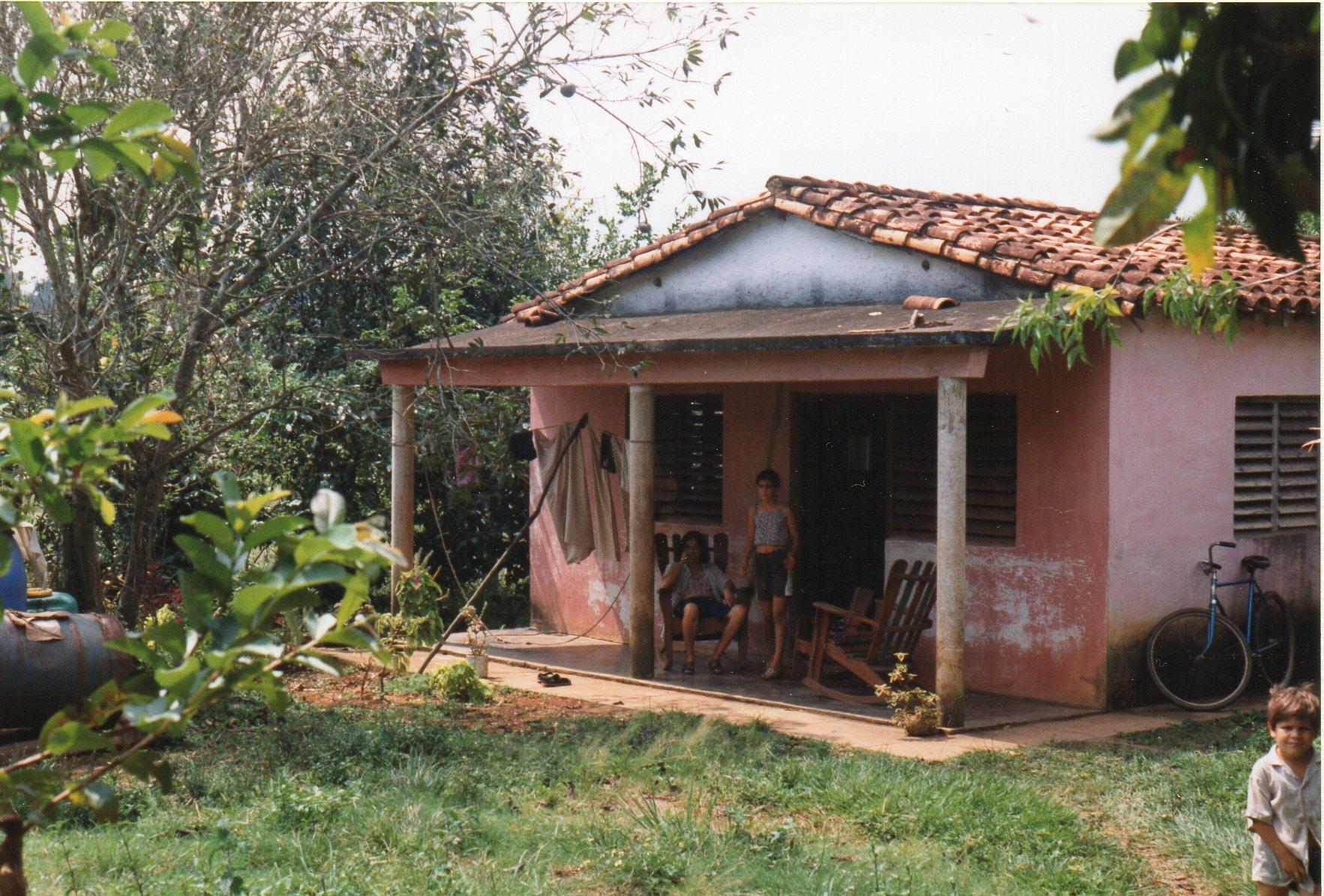 """Hus på landet i Viñalesdalen ved Pinar del Rio. Man ser her """"sydstatsterrassen"""" foran det lille hus, der tilhører en selvstændig tobaksavler. Castro sad dog tungt på økonomien, for avleren kunne kun sælge høsten til Staten."""