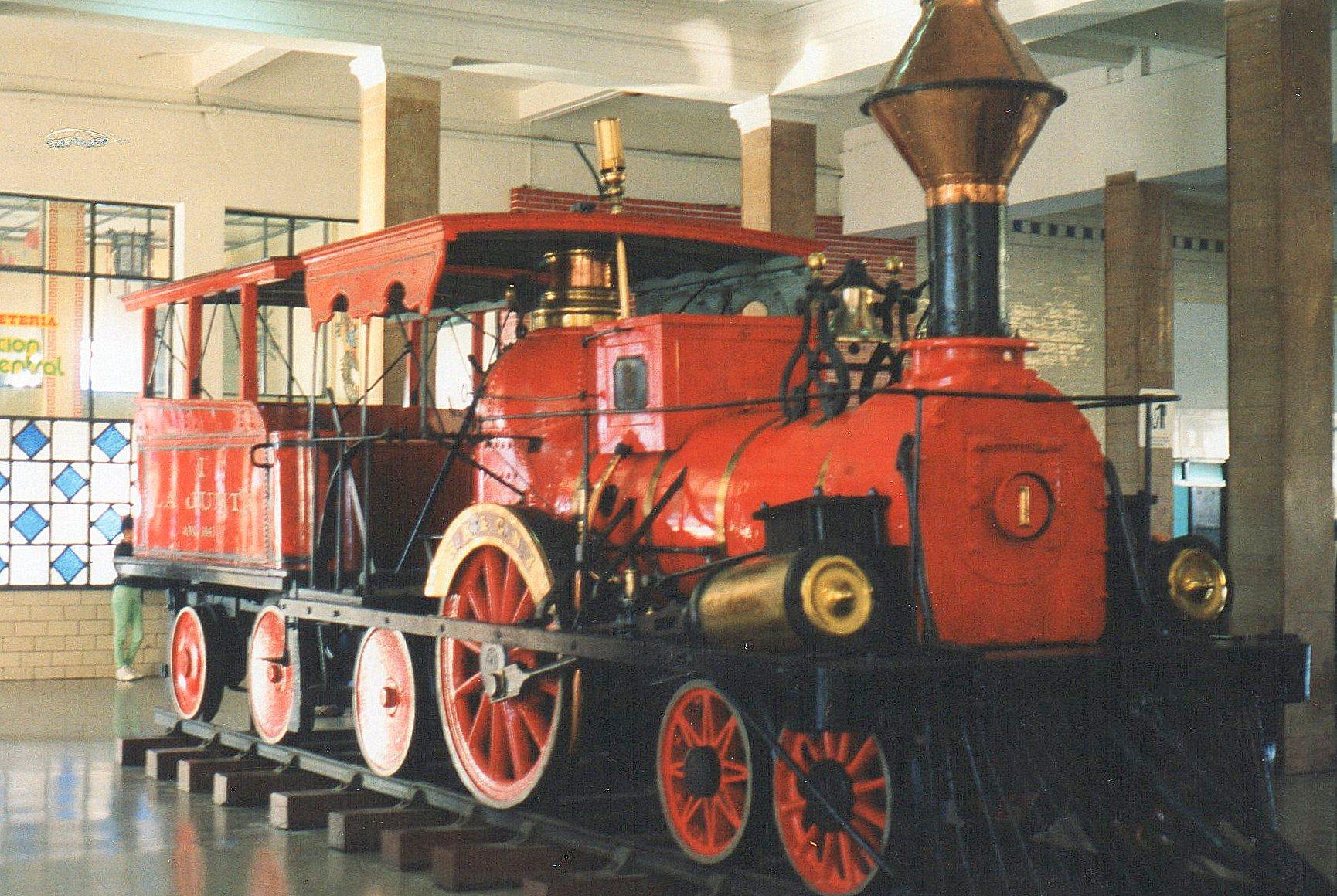 """De cubanske jernbaners først lokomotiv, """"La Junta"""" fra 1843, og således fire år ældre end de første danske lokomotiv og et år ældre end Altona - Kiels Banens første lokomotiv! Skærmen bar betegnelsen RK & GNJ. 2A1. Det fører tender med tag over! Det var opstillet på Havanas Hovedbanegård, hvor Castros forgænger, Batistas salonvogn også var udstillet."""