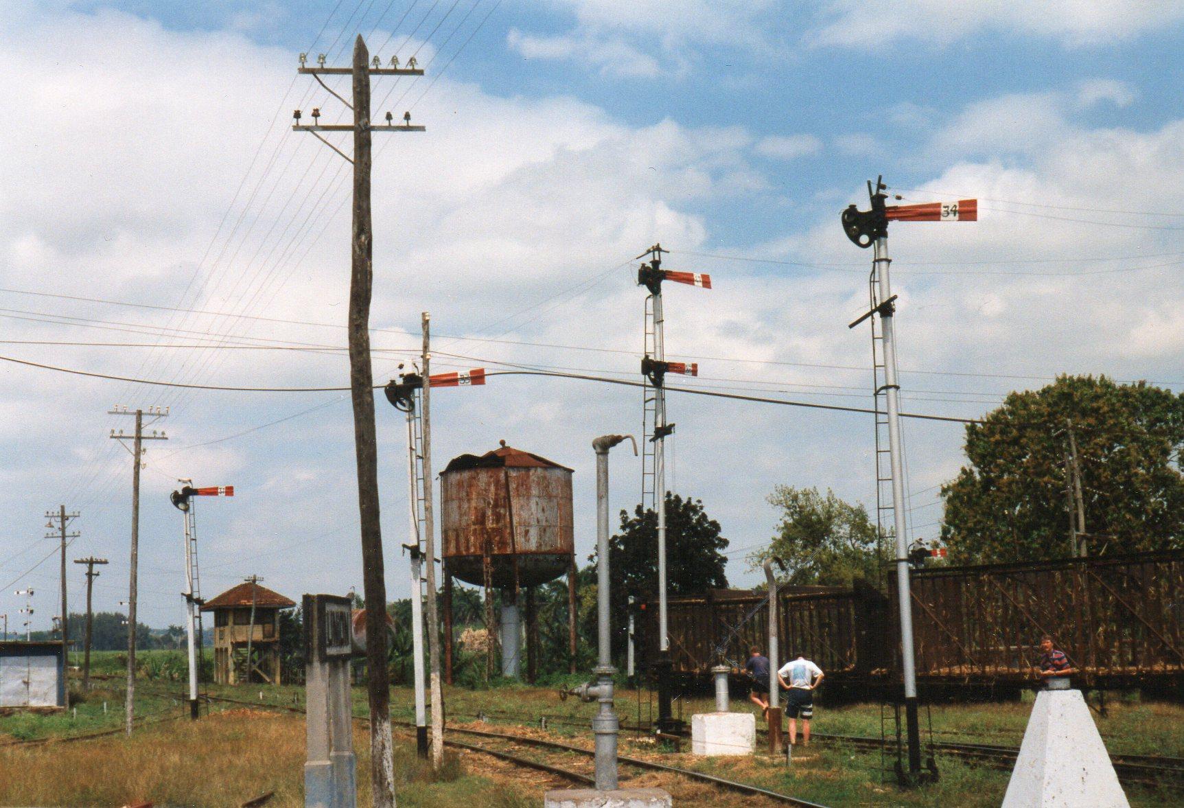 Udkørselssignaler for fire spor i Union de Reyes. Her var en gennemkørende FCC linje samt baner til tre sukkerfabrikker. Et par sukkerrørsvogne, et signalhus, en vandkran og et vandtårn ses også sammen med et par entusiaster.