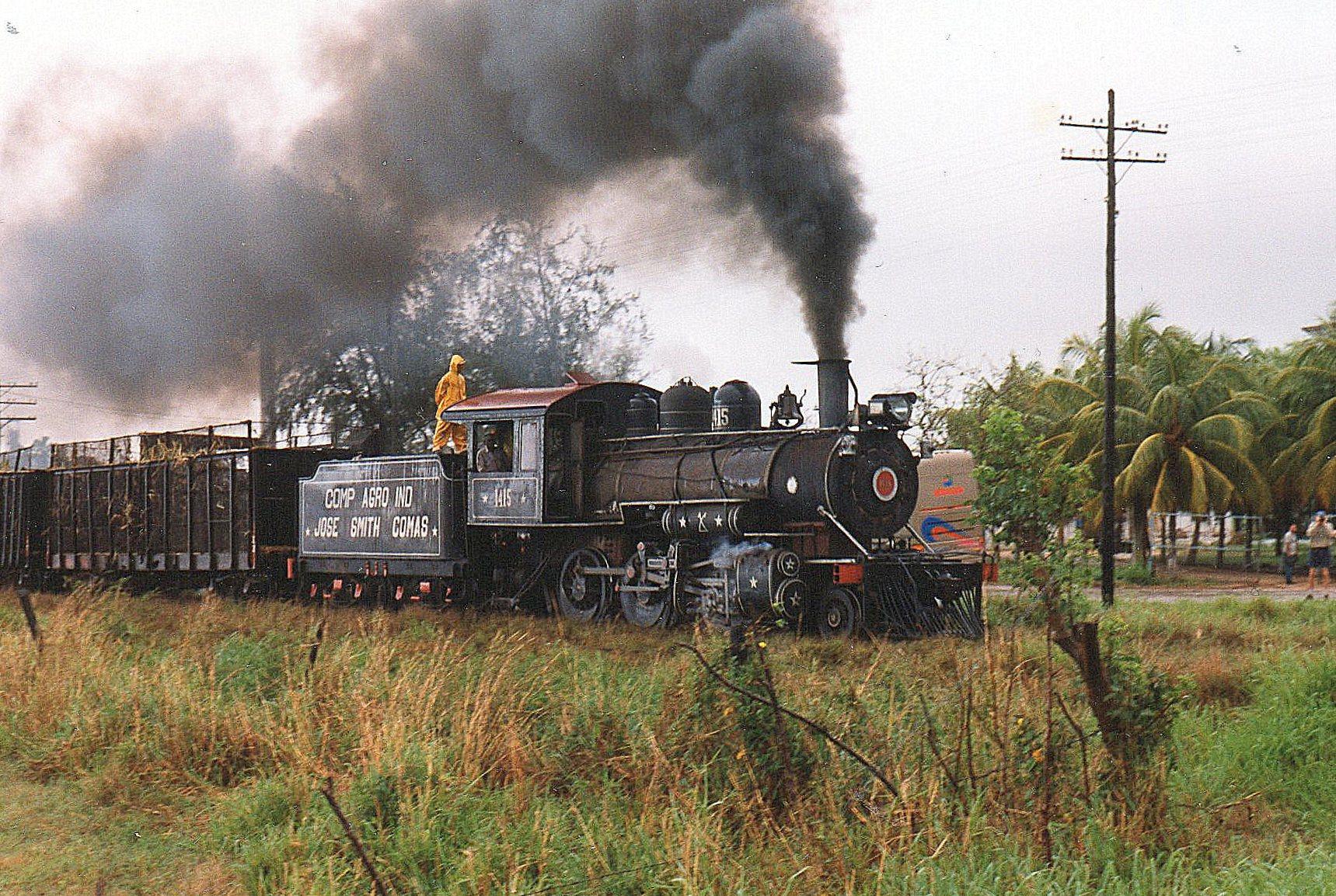 Senere regnede det, men himmelovertrækket dæmpede det stærke luys, så man her ser lokomotivet undervogn. Maskinen er CAI 315, Jose Smith Comas1415, Vulcan 3975/1920. 1'C. En medkørende frisker sig med et bad på tenderen.