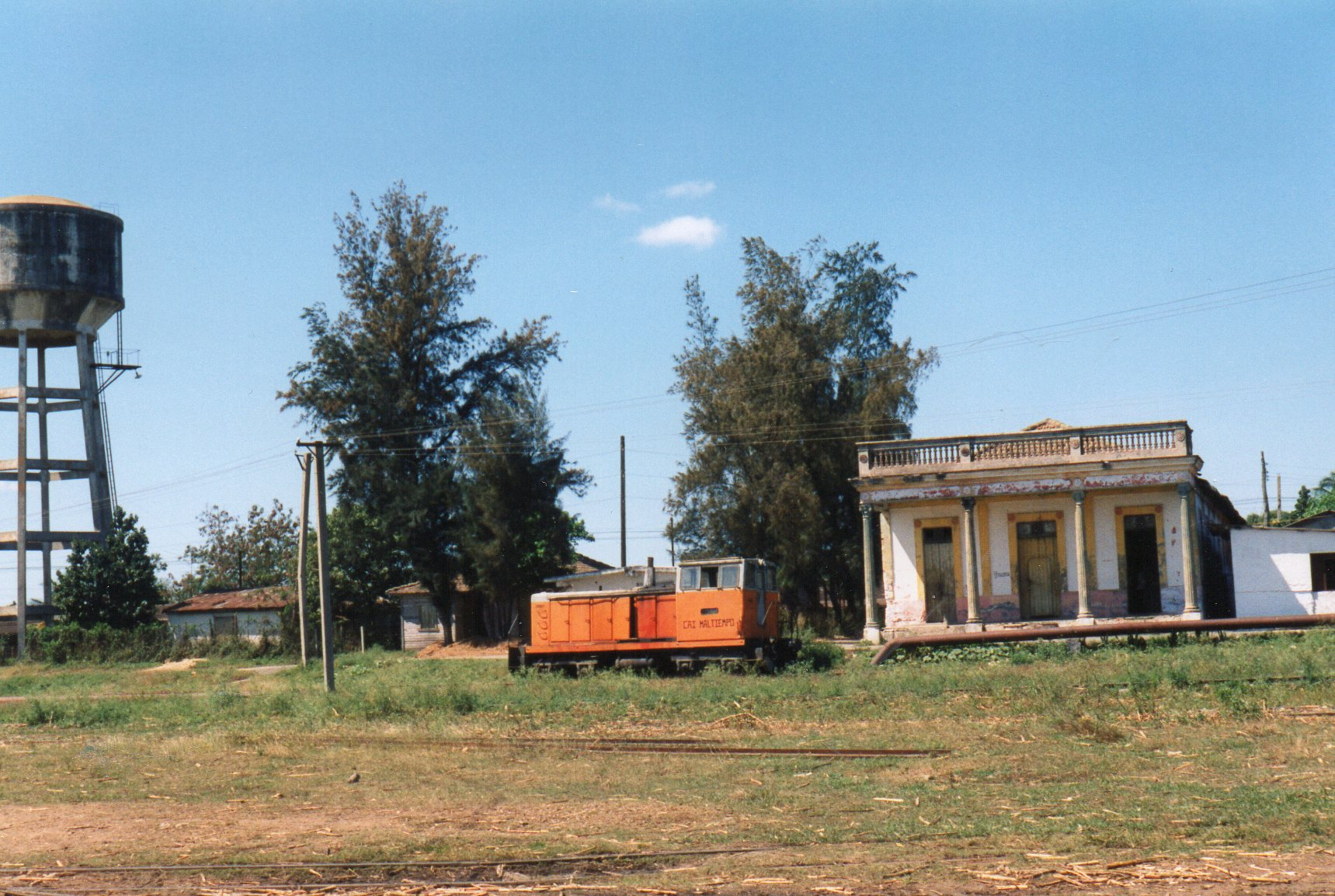 """På Mal Tiempo, der betyder dårligt Vejr! fald jeg åbenbart for diesellokomotiver, selm om jeg ikke nåede tæt nok på til at læse nummeret. Den var nemlig hensat. Af data har jeg: 762 mm. Kaluga type TU7. """"Stationsbygningens"""" arkitekt have åbenbart fundet en tegning af et græsk tempel og brugt det som forlæg."""