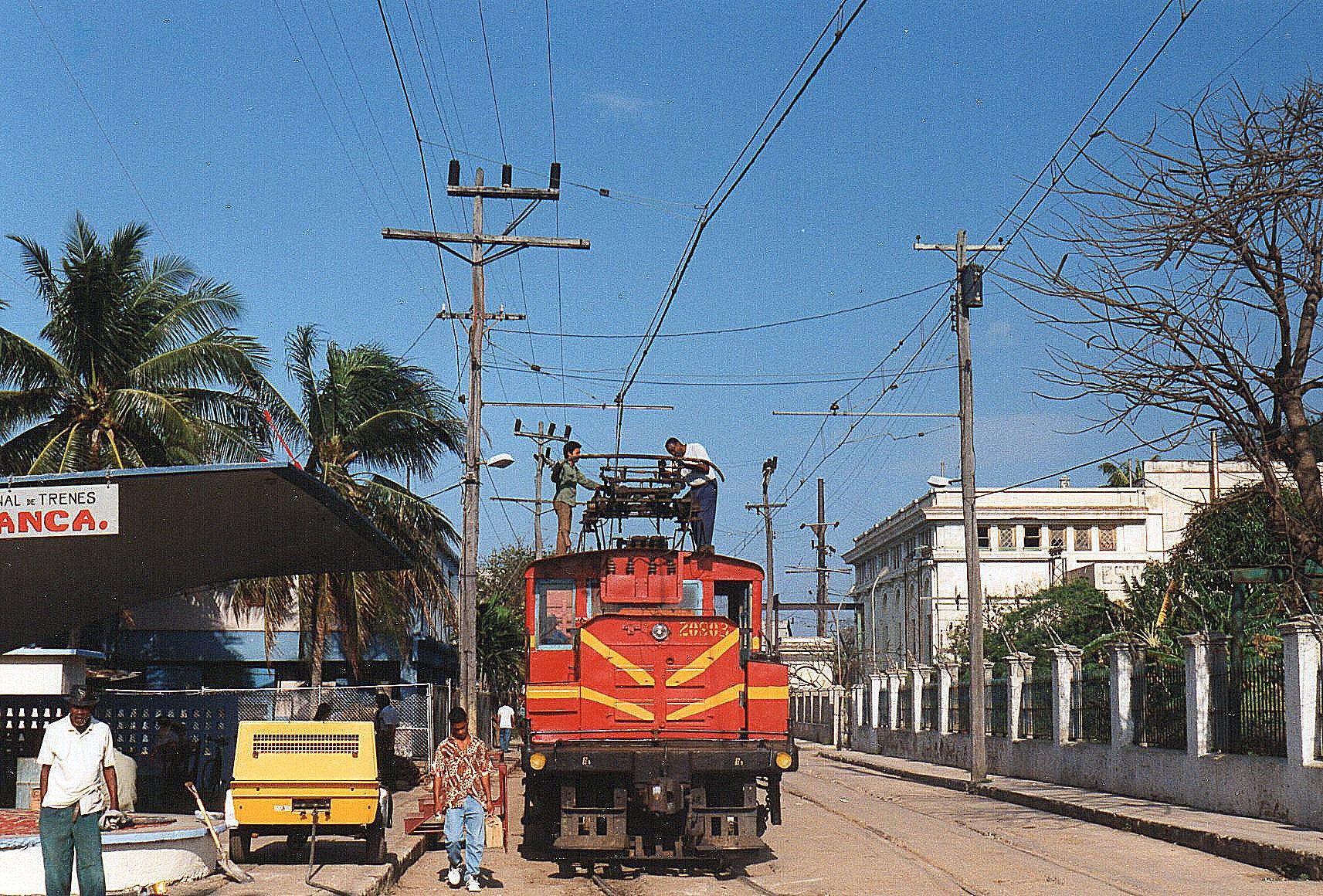 """Hersheybanen udgård fra Havanaforstaden Casablanca. Banen fører midt gennem gaderne, og stationen ligger også midt i gaden. Det aldrende lokomotiv havde manuel hævning af strømaftageren. Da jeg så dette syn, røg det ud af min Cubas beskæftigelsessituation in mente: Nå, det bruger nok engangspersonale!"""" Jeg havde dog set mændene afbryde strømmen, inden kravlede op på maskinen."""