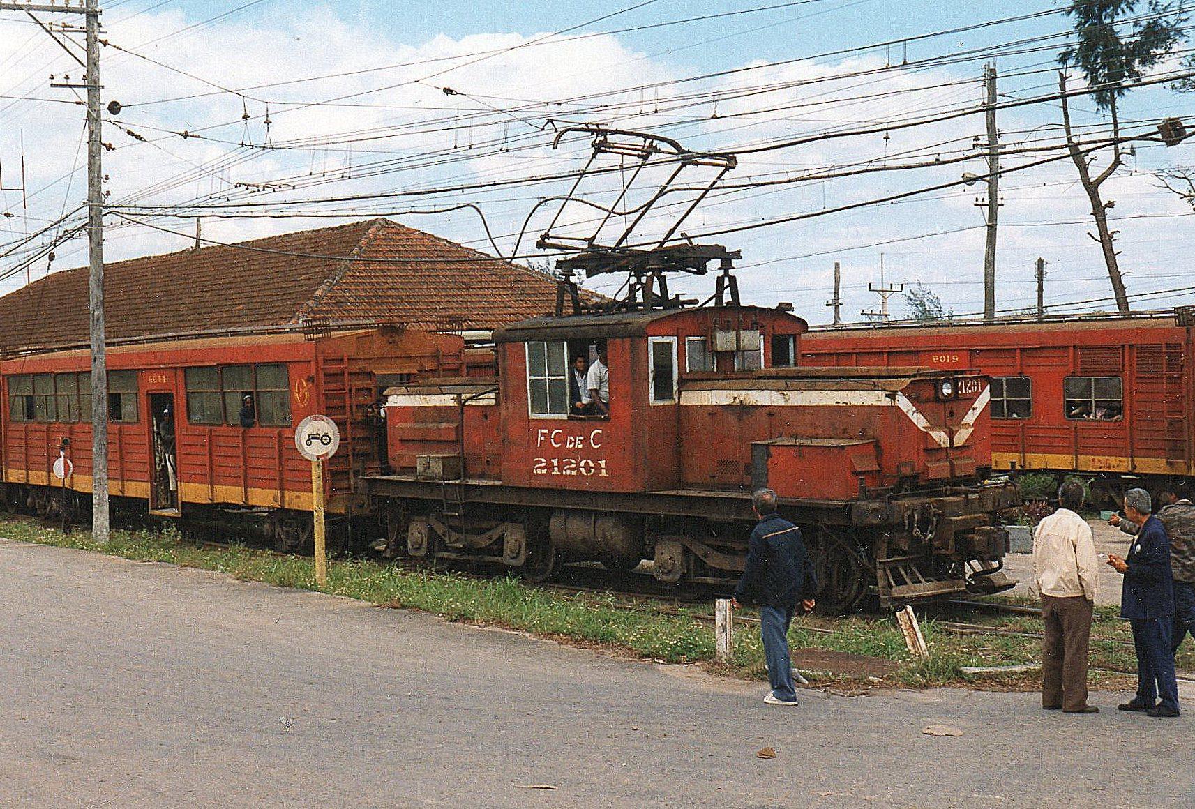 FCC 21201 også fra Generel Electric, men med ukendt byggenummer og -år i Calilo Cienfuegos. Vognene er ombyggede rumænske godsvogne. Toget krydsede her det tog, vi ankom med, der sås på modsatte perronside. Bemærk forbudsskiltet og traktoren!