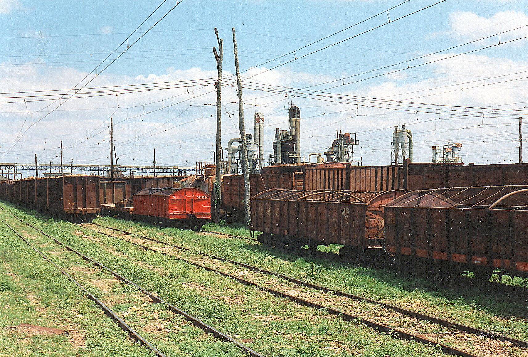 Mølle CAI 205 Camilo Cienfuegos og risten foran møllen med masser af vogne, både sukkerrørsvogne og almindelige godsvogne.